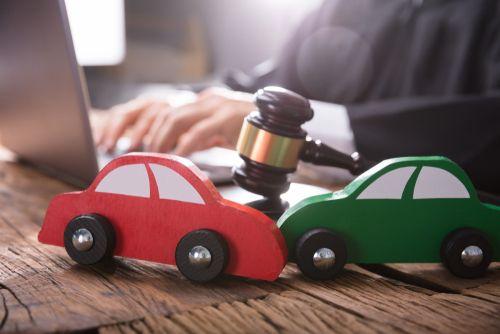 een rode en groene speelgoedauto botsen op elkaar op bureau van jurist