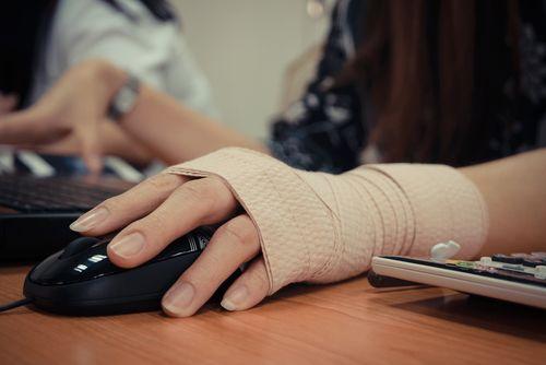 iemand bedient computermuis met een hand in het verband