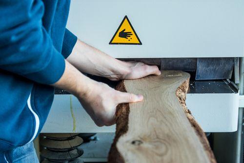 iemand schuift houten plank zonder beveiliging in gevaarlijke machine