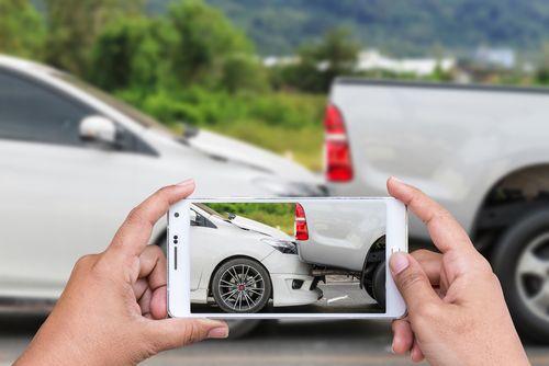 iemand neemt met smartphone foto van twee op elkaar gebotste auto's