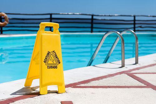 geel bordje dat waarschuwt voor gladde vloer aan de rand van zwembad