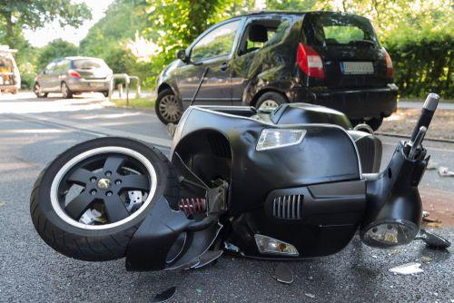 kapotte scooter ligt op de weg na aanrijding met auto