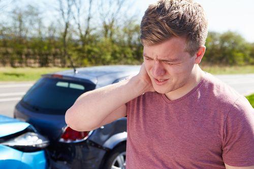 jonge man grijpt naar pijnlijke nek na botsing auto